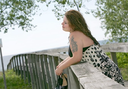 one beautiful plus size woman leaning against a pier near the beach
