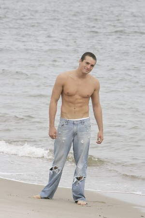 one shirtless young man standing on the beach full length portrait Stock Photo - 3974671