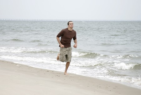 one young fit man running along the beach Stock Photo - 3974672