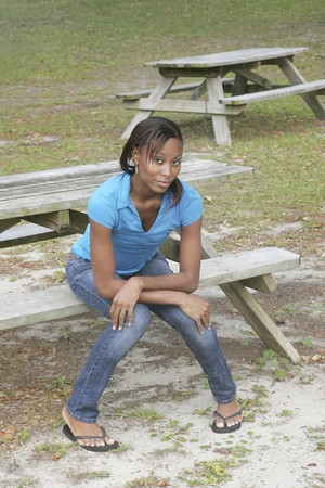 sit: one African American young woman dressed in blue sitting on a picnic table in the park Stock Photo