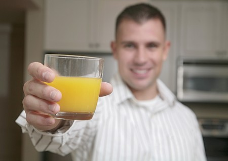 one young adult male holding a glass of orange juice toward the camera (focus on juice) Stock Photo - 4077732