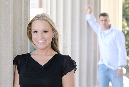 one young man and woman posing for engagement photos outdoors against columns 版權商用圖片