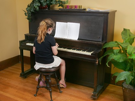 upright: one yougn child playing piano with sheet music Stock Photo