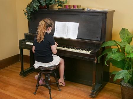 tocando piano: Un ni�o yougn a tocar el piano con las partituras Foto de archivo