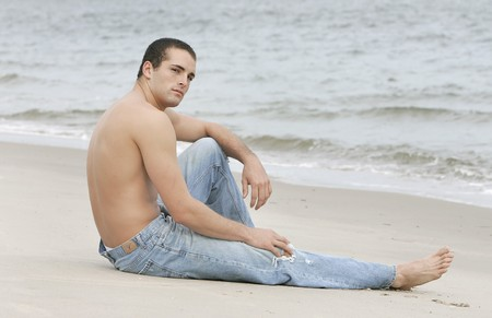 one fit athletic young man sitting on the beach relaxing photo