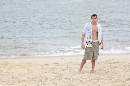 one young man standing on the beach full length portrait with lots of copyspace photo