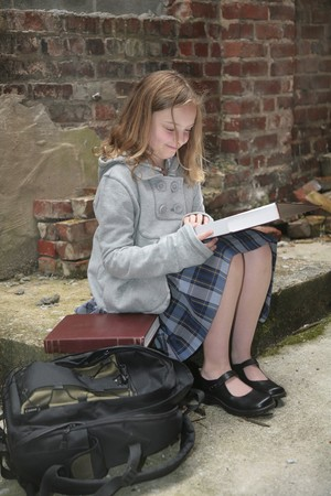 preteen girl: one young schoolgirl reading a book outdoors against a grungy brick background