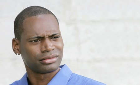 one disgusted looking shocked or surprised African American guy closeup portrait outdoors photo