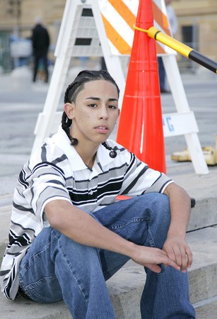 a young boy sitting on the stairs near construction warning signs photo