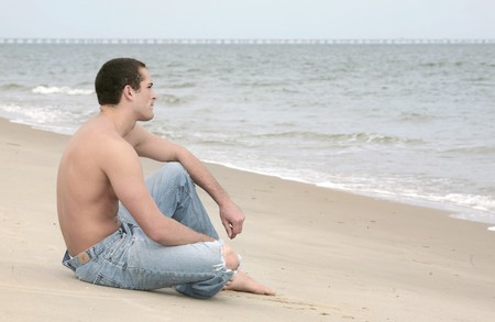 a young fit male sitting on the beach full length photo