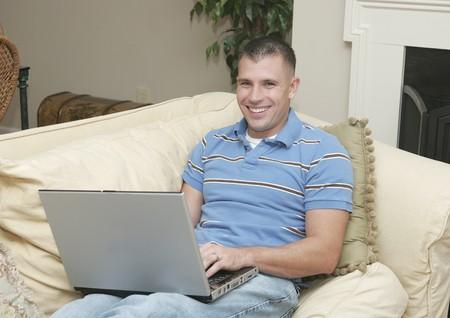 een jonge man werkt op een laptop computer met een openhaard thuis