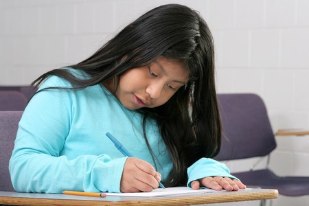 person writing: one young girl student writing in a classroom