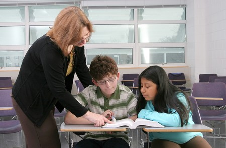 one woman teacher helping two young students in class Stock Photo - 4363388