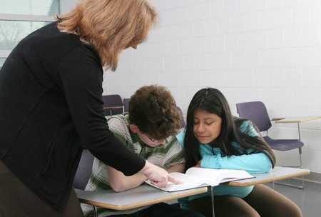 one woman teacher helping two young students in class
