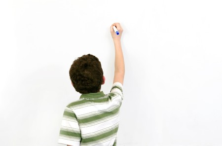 one young boy student writing on a blank whiteboard