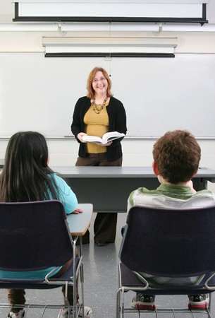 one woman teacher helping two young students in class Stock Photo - 4400155