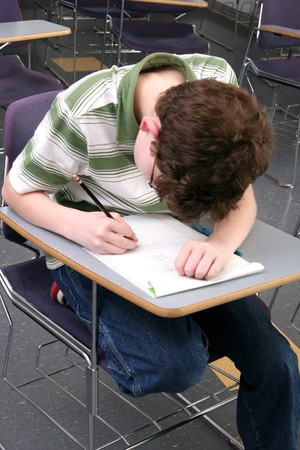 one young male student studying in class reading and writing photo