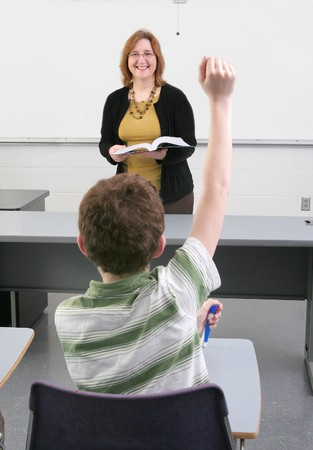 one woman teacher helping a young student in class photo