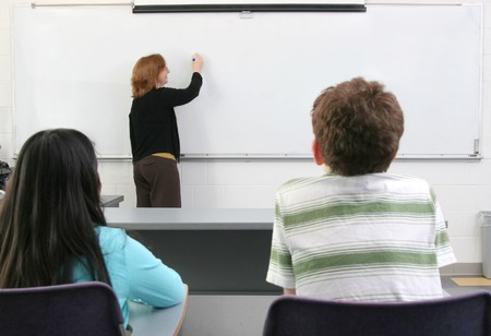 one woman teacher helping two young students in class Stock Photo - 4410917