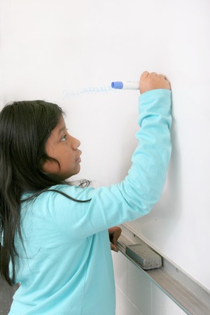 one young student writing on a blank whiteboard photo