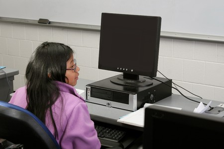 one young student girl studying on the computer in school photo