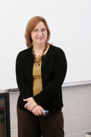 one adult female teacher pointing to a blank whiteboard photo