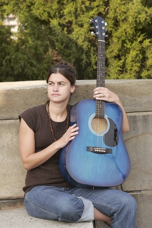 one young brunette woman holding a blue guitar looking thoughtful 스톡 콘텐츠