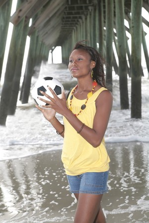 one attractive young African American woman with a soccer ball at the ocean photo