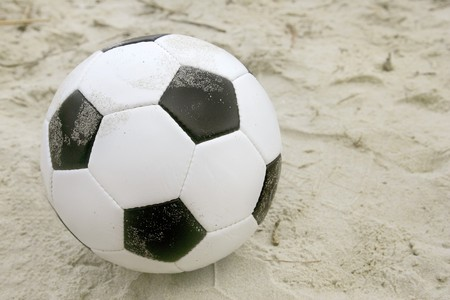 one dirty soccer ball sitting on the beach photo