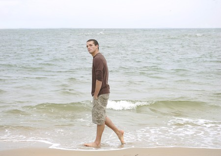 one young man walking on the beach full length portrait Stock Photo - 4444404