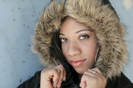 one young woman in a hooded jacket against a blue wall photo