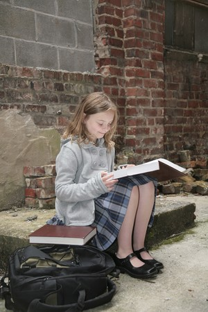one young schoolgirl reading a book outdoors against a grungy brick background Imagens - 4936316