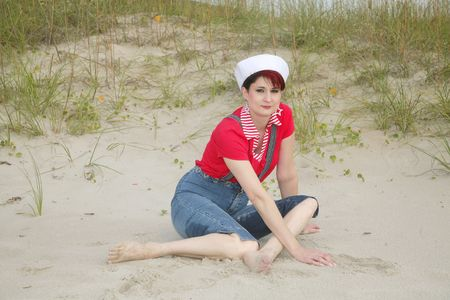one pretty woman in red white and blue nautical wear posing on the beach near a dune photo