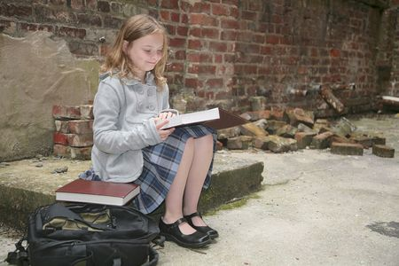 one young schoolgirl reading a book outdoors against a grungy brick background