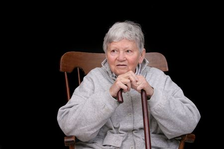 one elderly adult female sitting in a rocking chair holding her cane photo