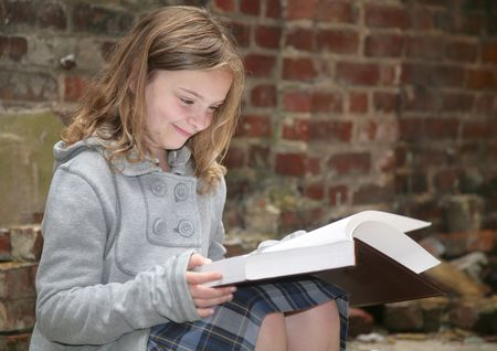 one young schoolgirl reading a book outdoors against a grungy brick background photo