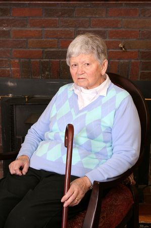 one elderly adult female sitting in a chair near the fireplace photo