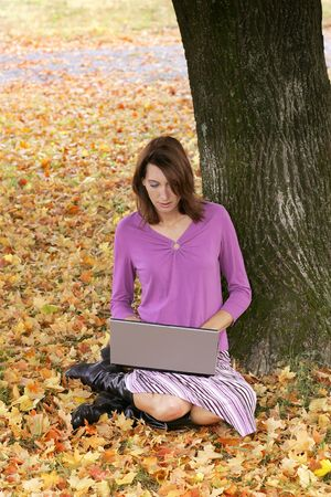 one young brunette woman sitting in the colorful fall leaves working on a laptop computer outdoors photo