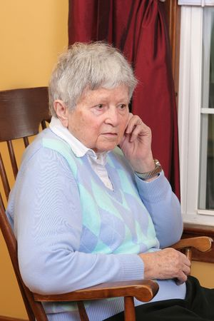 one elderly adult female sitting in a rocking chair  photo