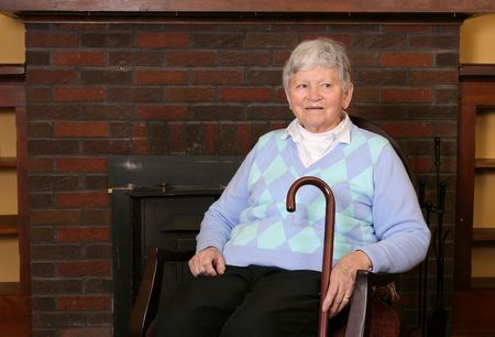 one elderly adult female sitting in a chair near the fireplace Stock Photo - 4989406