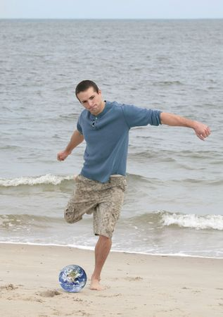 one young athletic man with a soccer earth ball on the beach ready to play photo