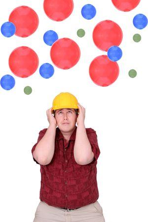 agachado: un expresivo hombre adulto trabajador de la construcci�n eludir la ca�da de las bolas con hardhat m�s de blanco Foto de archivo