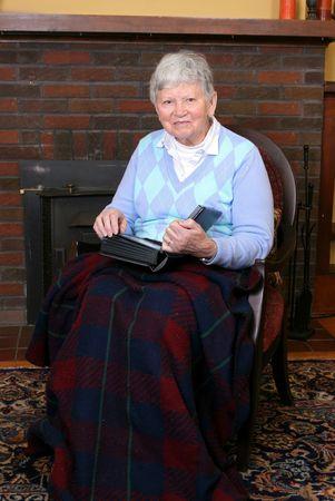 un adulto mayor femenino sentado en una silla cerca de una chimenea Foto de archivo - 5016479