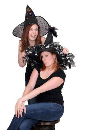 pretend: 2 pretty young women dressed as witches with black hats over white Stock Photo