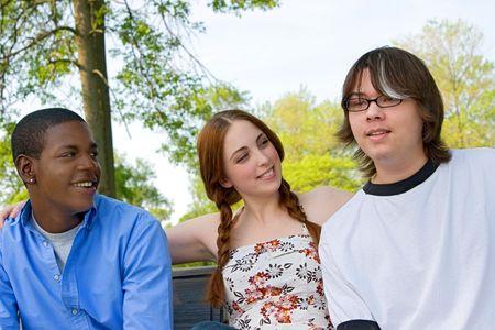 waistup: Waist-up de tres adolescentes sentados lado a lado al aire libre. Formato horizontal.