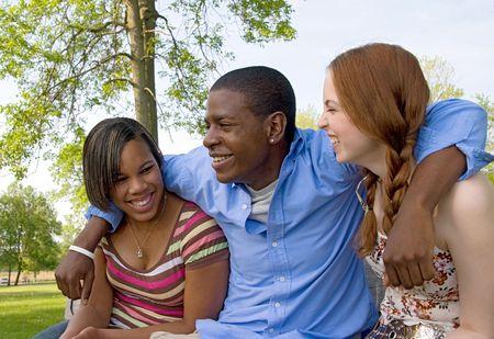 waistup: Waist-up de tres adolescentes al aire libre, sentados lado a lado y riendo. Formato horizontal.