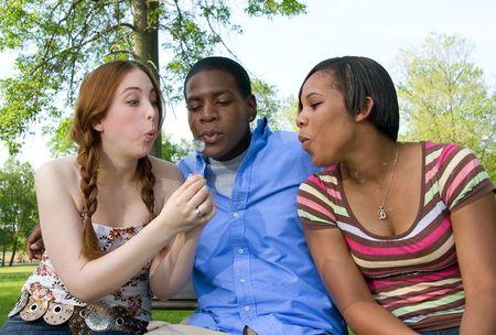 waistup: Waist-up de tres adolescentes al aire libre, sentados lado a lado y soplando la pelusa fuera un diente de le�n. Formato horizontal.