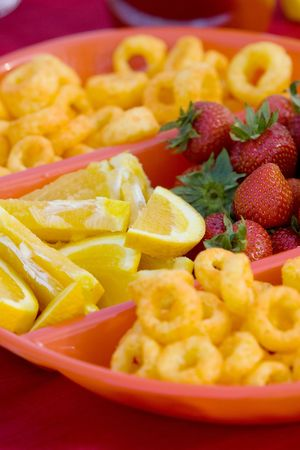 Close-up of strawberries, lemon slices, and cheese curls in a divided bowl. Vertical format. Stock Photo - 5795267