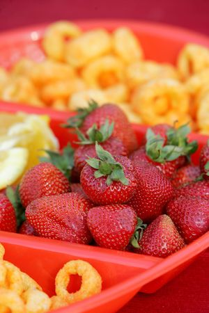 Close-up of strawberries, orange slices, and cereal in a divided bowl. Vertical format. photo