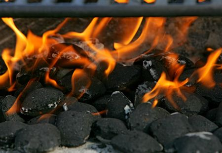 Close-up view of charcoal briquettes and flames, with the edge of the grill visible at the top of the frame. Horizontal format. Stock Photo